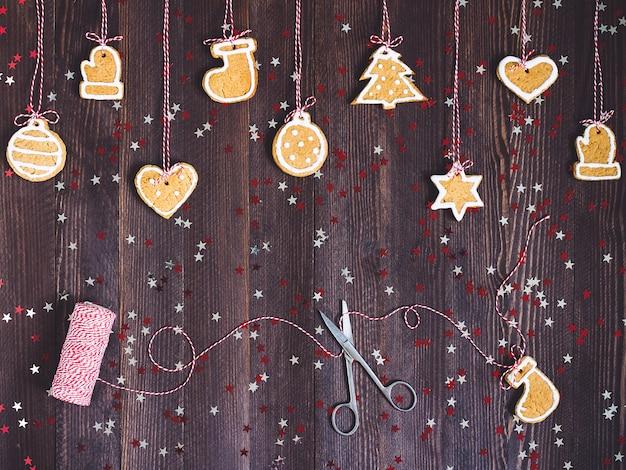Biscuits pain d'épice sur corde pour la décoration de sapin de noël avec des ciseaux et du fil de nouvel an sur table en bois Photo gratuit