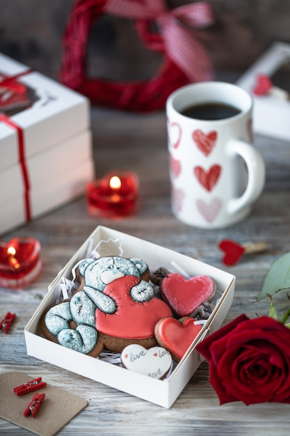 Biscuits De Pain D'épice Dans Une Boîte Cadeau Avec Bougies, Rose Et Tasse à Café Photo Premium