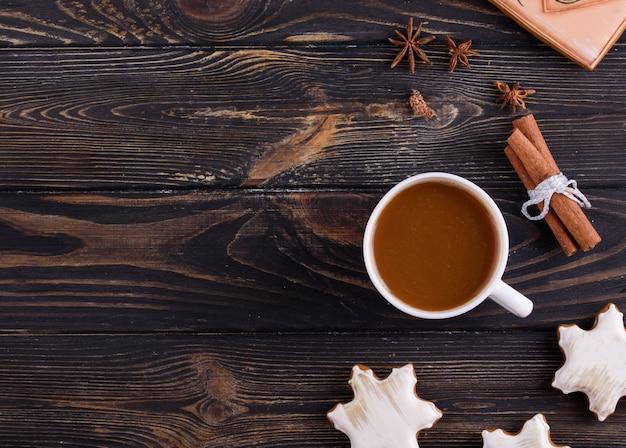 Biscuits de pain d'épice de noël sur un fond en bois avec des bâtons de café et de cannelle aromatiques Photo Premium