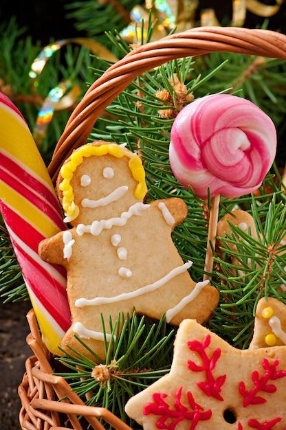 Biscuits De Pain D'épice De Noël Et Sucettes Dans Un Panier Sur Fond De Bois Ancien Photo Premium