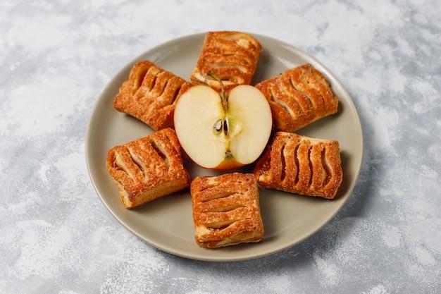 Biscuits de pâte feuilletée remplis de confiture de pommes et de pommes rouges fraîches sur du béton léger Photo gratuit