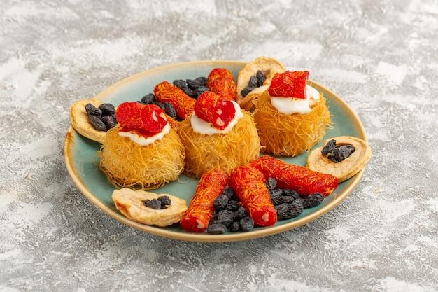 Biscuits Pâtissiers De L'est à L'intérieur De La Plaque Verte Avec Des Fruits Secs à La Crème Blanche Et Peu De Confitures Photo gratuit