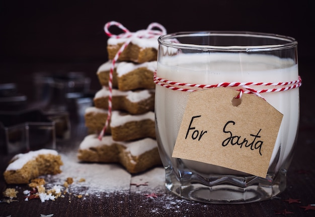 Biscuits pour le père noël avec verre de lait avec étiquette pour le père noël et arbre de noël Photo gratuit