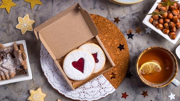 Biscuits ronds avec de la confiture en forme de coeur dans une boîte cadeau parmi les décorations de noël Photo Premium