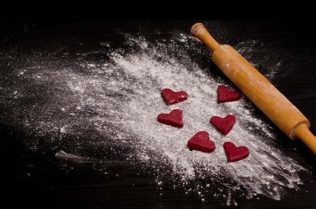 Biscuits rouges en forme de coeur sur une farine, cuisant le jour de la saint-valentin Photo Premium