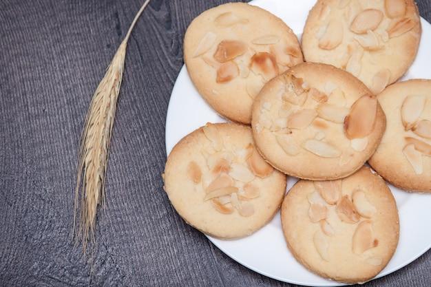 Biscuits savoureux biscuits aux amandes et au blé sur la plaque sur fond en bois. Photo Premium