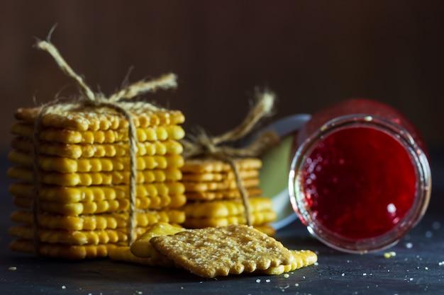 Les biscuits sont attachés avec une corde de chanvre et une bouteille de confiture de fraises sur la table dans le noir Photo Premium