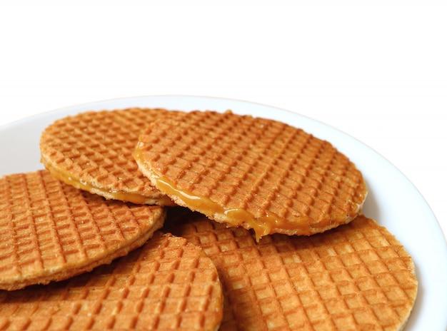 Biscuits stroopwafel, bonbons traditionnels néerlandais servis sur une plaque blanche isolée sur fond blanc Photo Premium