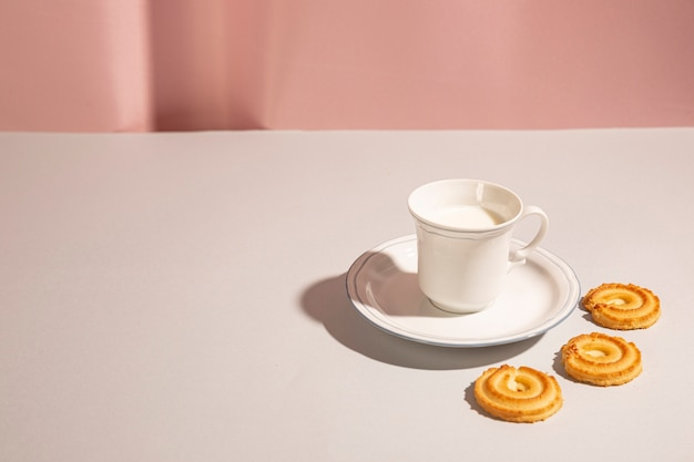 Biscuits sucrés disposés autour d'une tasse de lait sur un bureau blanc Photo gratuit