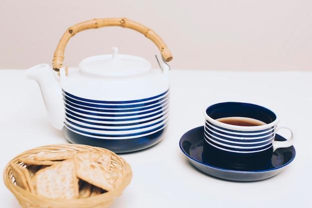 Des biscuits; tasse à thé et théière sur bureau blanc Photo gratuit
