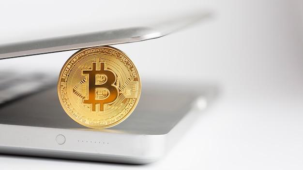Bitcoin close-up avec un ordinateur portable défocalisé Photo gratuit