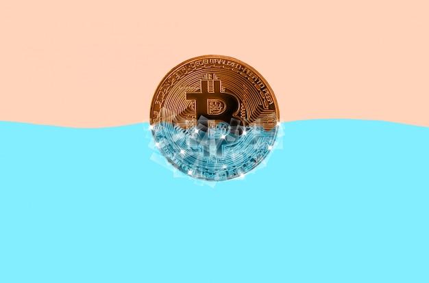 Bitcoin doré gelé dans des blocs de glace dans de l'eau bleue Photo Premium