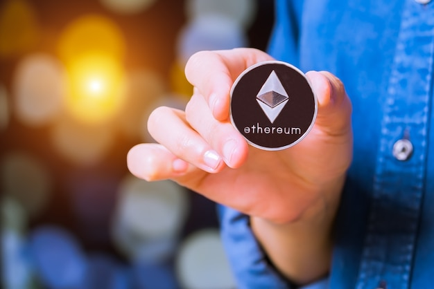 Bitcoin, ethereum, litecoin, ondulation. les femmes tiennent la monnaie de crypto-monnaie en main Photo Premium