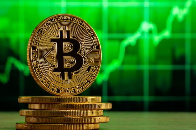 Bitcoin Physique Debout Sur Une Table En Bois Devant Un Graphique Vert Photo Premium
