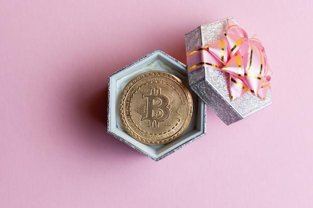 Bitcoin se trouve dans une petite boîte cadeau sur fond rose. Photo Premium