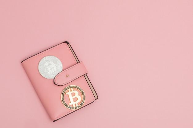 Bitcoins sur un portefeuille rose sur le rose avec fond Photo Premium