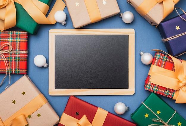 Blackboard maquette avec cadeaux chirstmas Photo gratuit