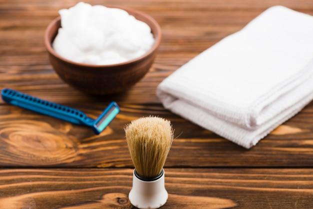 Blaireau classique devant le bol en mousse; serviette blanche pliée et rasoir sur un bureau en bois Photo gratuit