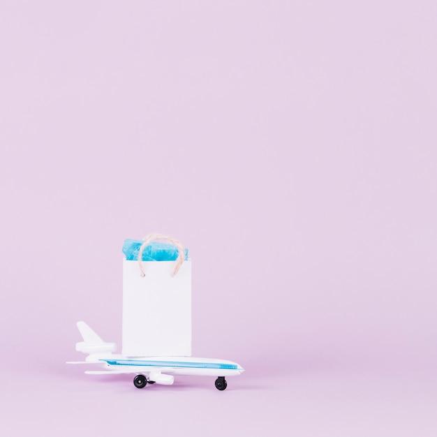 Blanc petit sac à provisions sur avion jouet sur fond rose Photo gratuit