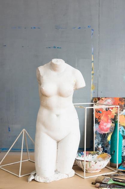 Blanc vieille statue féminine brisée et matériel de peinture Photo gratuit