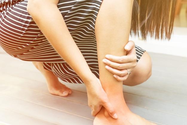 Blessure à la cheville / douloureuse, les femmes touchent la jambe douloureuse Photo Premium