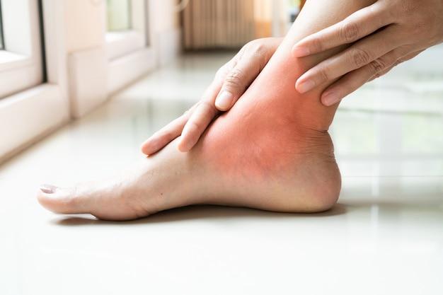 Blessure à la cheville de la femme / douloureuse, les femmes touchent la jambe à la cheville Photo Premium