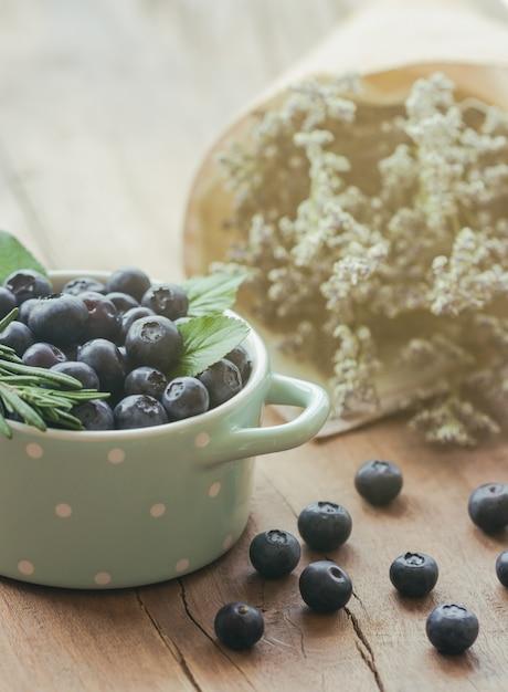 Bleuets sauvages frais dans un bol sur la table en bois sous le soleil Photo Premium
