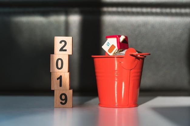 Bloc de bois année 2019 et maison miniature dans un seau rouge avec des pièces de pile Photo Premium