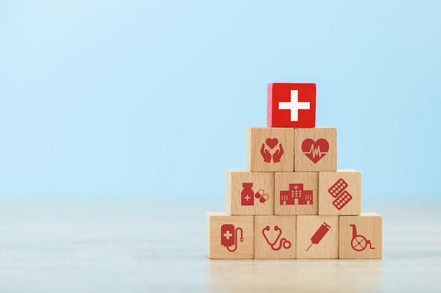 Bloc de bois d'assurance maladie empiler avec l'icône de soins de santé médical. Photo Premium