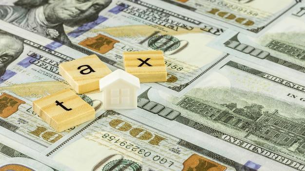 Bloc en bois et petit modèle de maison sur billets d'un dollar. concept fiscal. Photo Premium