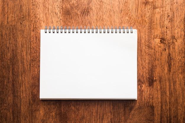 Bloc-notes blanc sur une table en bois antique ou âgé Photo Premium