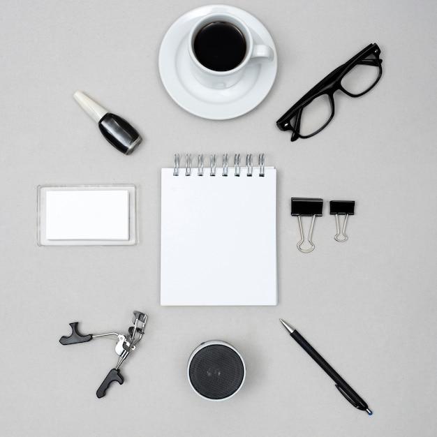 Bloc-notes blanc vierge entouré d'une tasse à café; vernis à ongles; recourbe-cils; orateur; stylo et trombones au-dessus de fond gris Photo gratuit