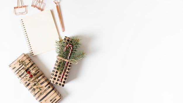 Bloc-notes avec des boîtes-cadeaux sur la table Photo gratuit