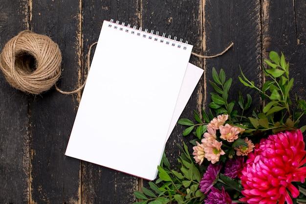 Bloc-notes avec un bouquet de fleurs sur un bois vintage foncé Photo Premium