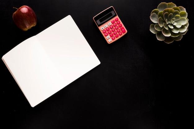 Bloc-notes avec calculatrice sur un bureau noir Photo gratuit