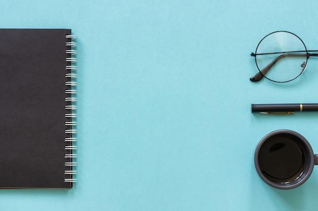 Bloc-notes de couleur noire, tasse de café, lunettes, stylo sur bleu Photo Premium