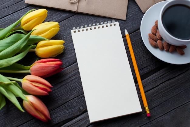 Bloc-notes avec un crayon à côté des tulipes, du café et des enveloppes. Photo Premium
