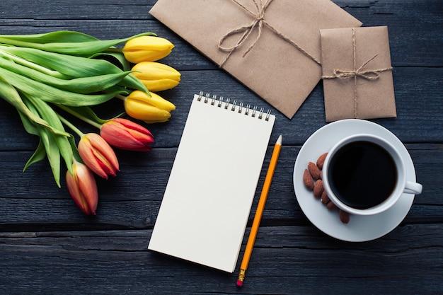 Bloc-notes avec un crayon à côté des tulipes. Photo Premium