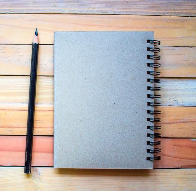 Bloc-notes avec un crayon sur fond de planche à bois.usage fond d'écran pour l'éducation Photo Premium
