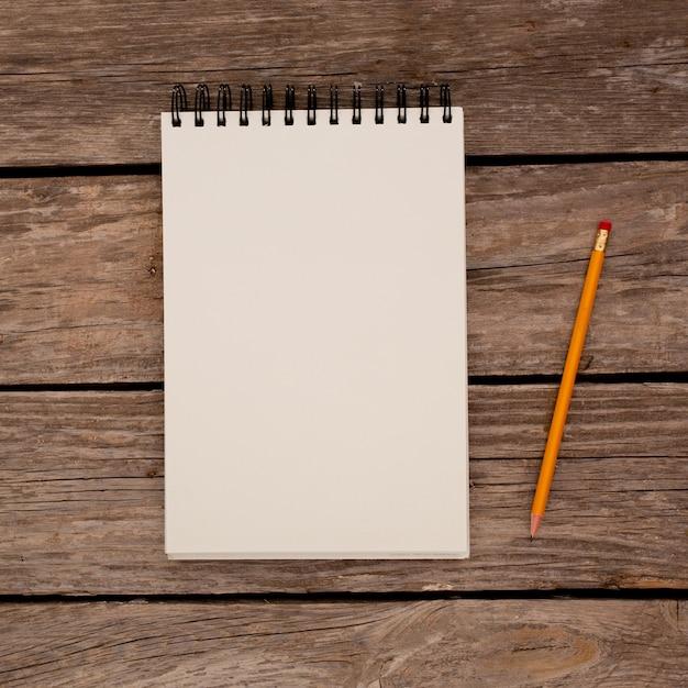 Bloc-notes Avec Un Crayon Sur Fond De Planche De Bois Photo gratuit
