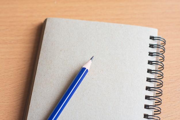 Bloc-notes avec un crayon sur la planche en bois background.using papier peint pour l'éducation, photo d'entreprise. prenez note du produit pour livre avec papier et espace de concept, objet ou copie. Photo Premium
