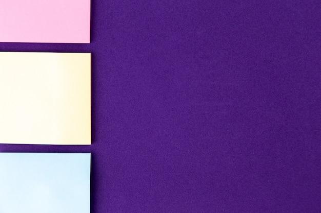 Bloc-notes avec ensemble de trombones colorés sur violet Photo Premium