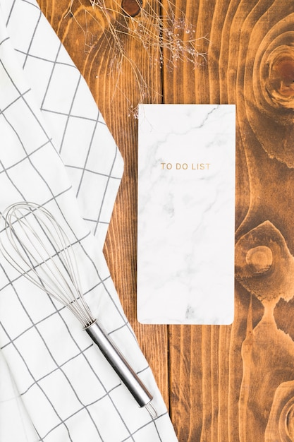 Bloc-notes avec fouet et serviette à carreaux sur une planche texturée Photo gratuit