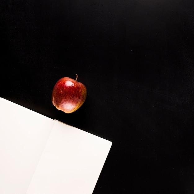Bloc-notes avec des fruits sur un bureau noir Photo gratuit
