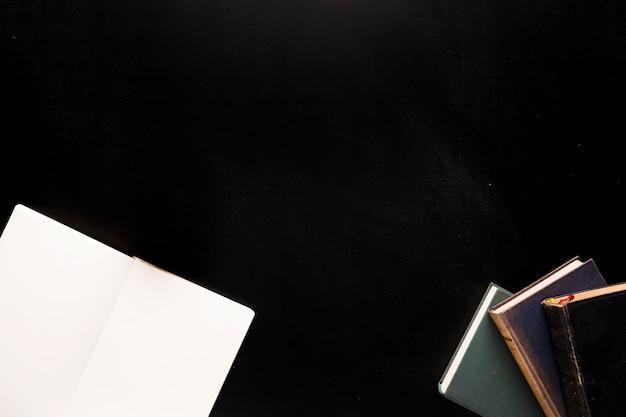 Bloc-notes et livres sur un bureau noir Photo gratuit