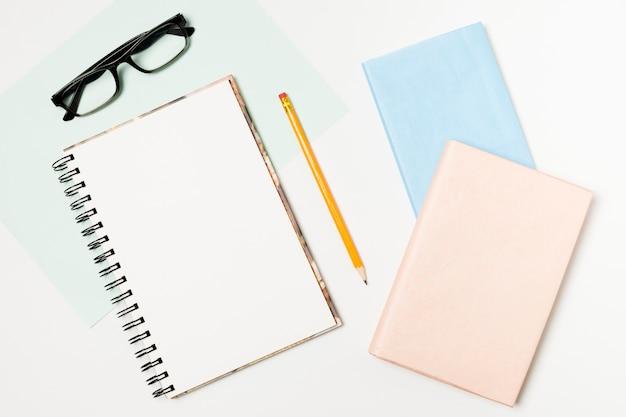 Bloc-notes et lunettes vue de dessus Photo gratuit