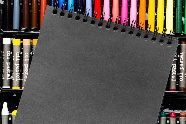 Bloc-notes Noir Et Marqueurs Et Crayons Colorés Photo gratuit