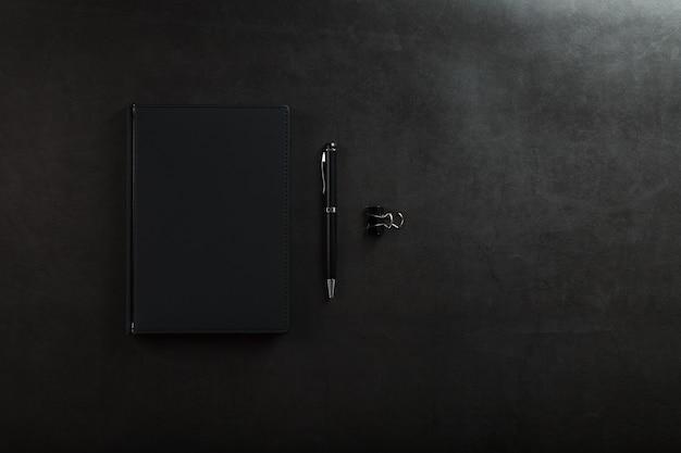 Bloc-notes Noir Avec Un Stylo Noir Sur Fond Noir. Vue De Dessus, Concept Minimaliste. Espace Libre. Photo Premium