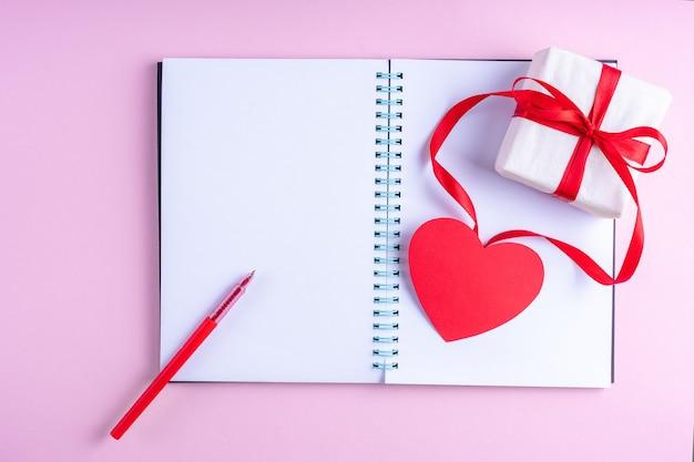 Bloc-notes Ouvert Blanc Blanc, Stylo Rouge, Boîte-cadeau Avec Ruban Rouge Et Forme De Coeur En Papier Rose Photo Premium