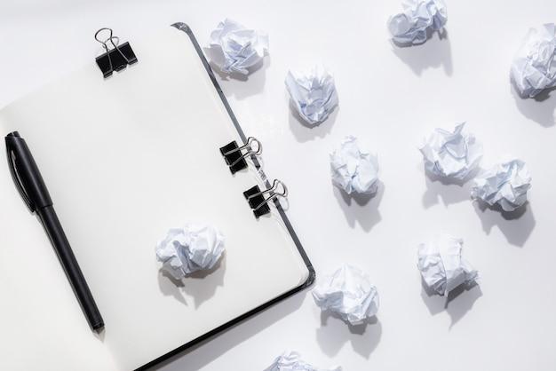 Bloc-notes ouvert sur un fond blanc avec des papiers froissés Photo Premium